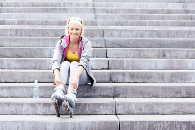 Woman with roller blades sitting on stairs