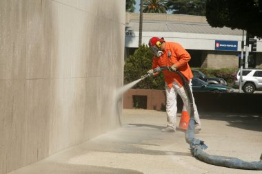 An unidentifiable city worker sand blast away graffiti on a wall