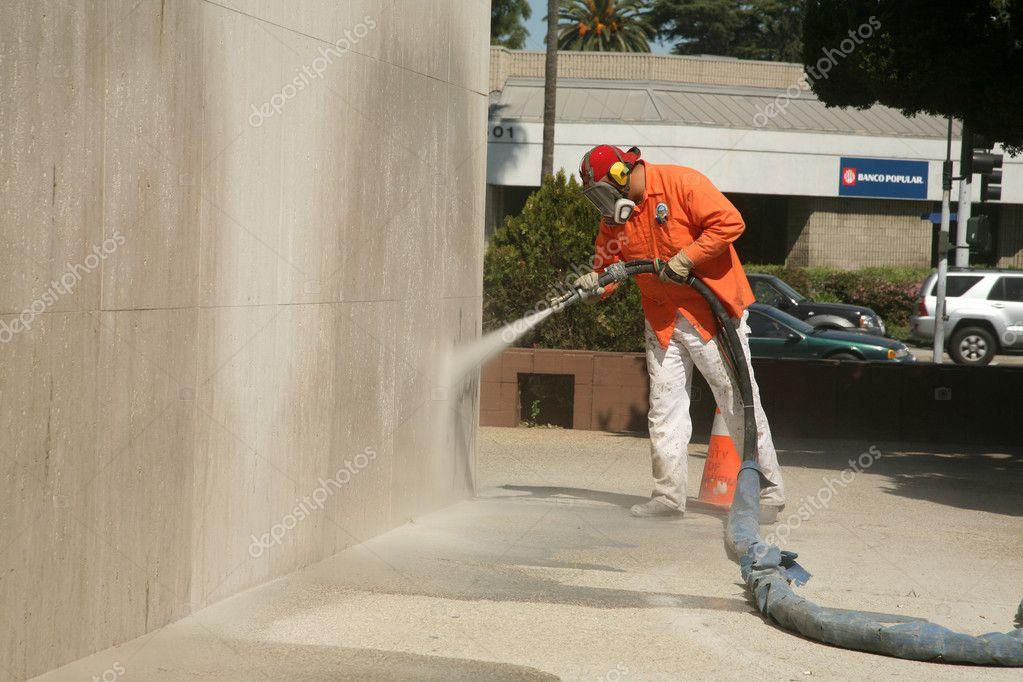 An unidentifiable city worker sand blast away graffiti on a wall