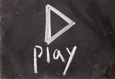 play sign drawn with chalk on blackboard