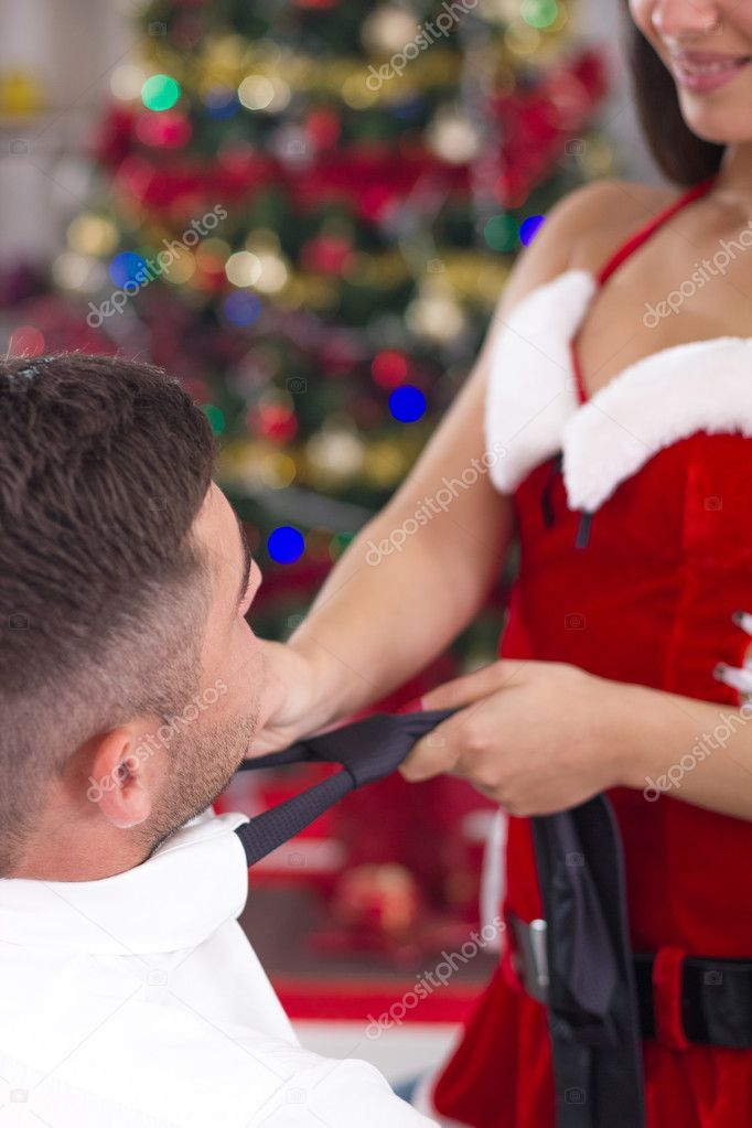 Sexy santa woman pulling tie of man on Christmas Eve
