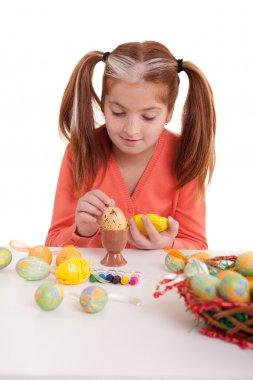 Little girl painting easter eggs