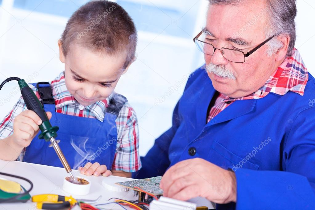 Grandfather teaching grandchild to use soldering resin