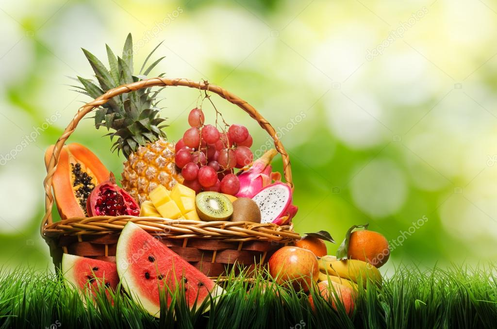 Basket of tropical fruits on green grass