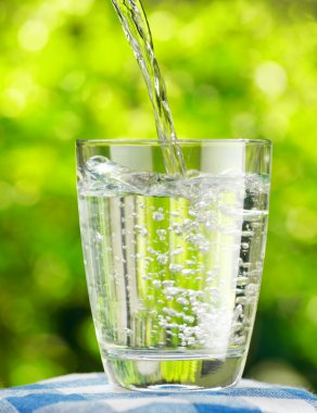 Glass of water on nature background