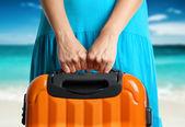 Fotografie Frau im blauen Kleid hält orange Koffer in Hand am Strand
