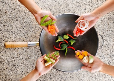 Four hands puts fresh vegetables in the wok. Cooking concept
