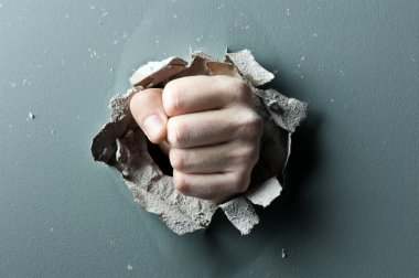A wall is broken through by a fist stock vector