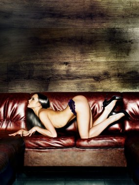 Portrait of a beautiful naked young woman on a leather sofa