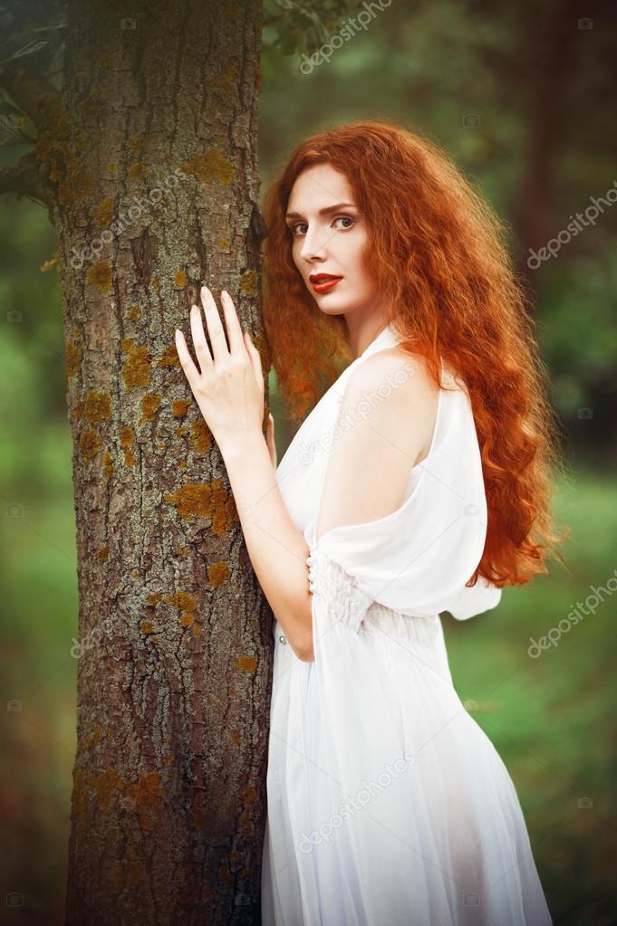 Beautiful redhead woman wearing white dress stands near tree