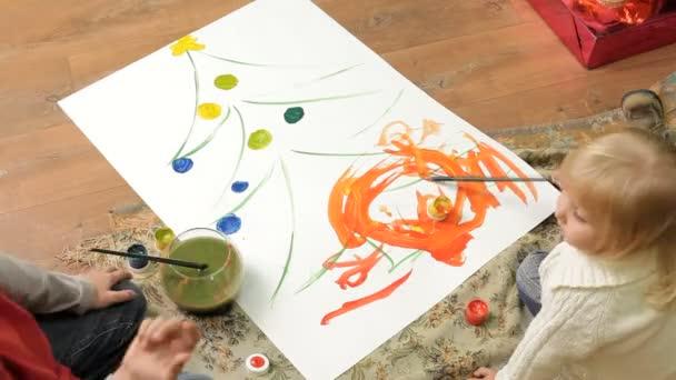 Kinder malen auf Leinwand. zwei kleine Kinder sitzen auf dem Boden und malen ein Weihnachtsbaum