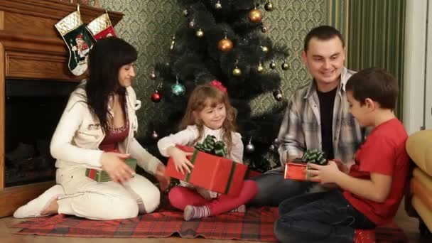 A family gathered together near a Christmas tree. Presents for Christmas.