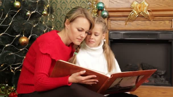 Mother reading a story to her daughter under a Christmas tree. Reading a story.