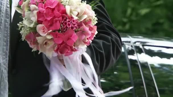 ženich a nevěsta drží svatební kytice otáčením
