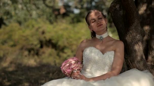ein schönes Mädchen saß unter einem Baum mit einem Blumenstrauß