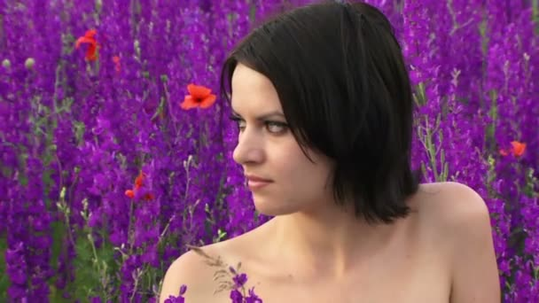 Beautiful girl on the field of lupine. Sexy girl sits on a beautiful field of purple flowers and smiles.