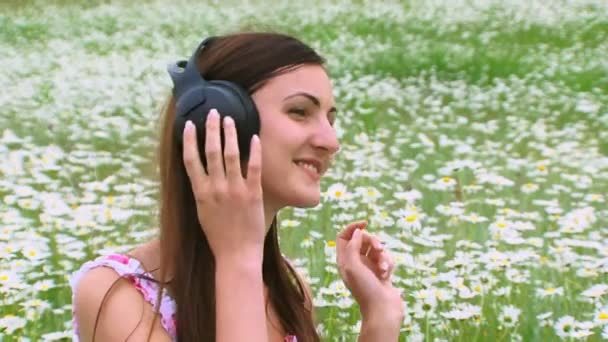 A girl listens to music on the field. A young girl listens to music on the nature through the large headphones on the background field daisies.