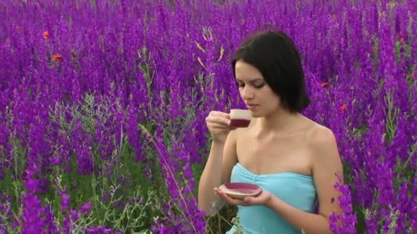 Woman drinking tea in the field. Beautiful girl drinking tea in nature among the purple flowers.
