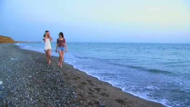 dvě dívky se sluchátky. dvě hezké dívky jít na pláž a střídavě poslouchat hudbu prostřednictvím velkých sluchátka