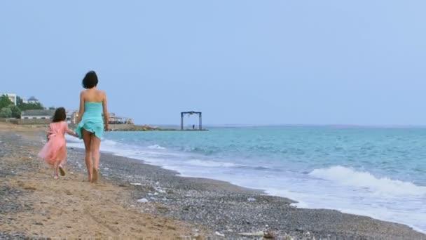 dvě procházky podél pobřeží. dospělé ženy a malé dítě běží do dálky moře pláž