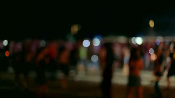 Disco outdoors. A large group of young dancing under the night sky. Defocused