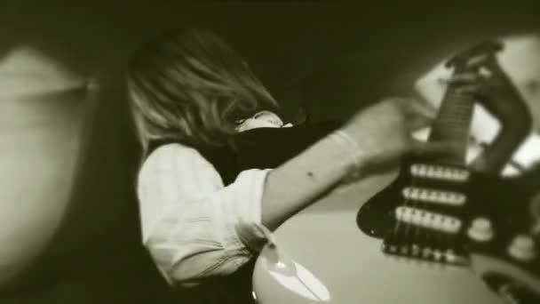 rock and roll lány. egy hosszú hajú lány aktívan játszik a gitár. fekete-fehér filmek.
