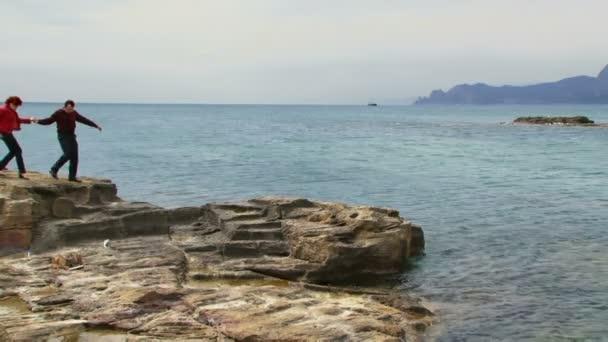 párok sétára, a sziklák. egy fiatal pár megy a rock ellen a tenger.