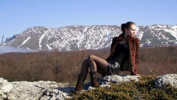 žena v horách. krásná dívka modelka sedí na skále proti krásné přírodní scenérie. dvě snímek. detail.