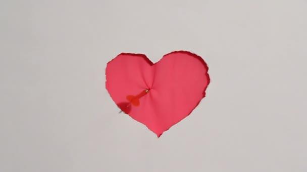 piros szív lóg a falon. Valentin-nap témája. HD. piros szív lóg a falon, és a két dart kap-ba ez. közelről. fehér háttér.
