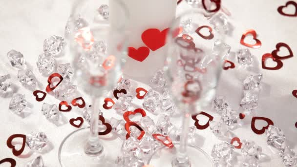 Valentines day theme. HD. Small hearts fall on the wineglasses.Close up. white background.