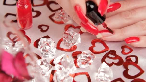 dívka maluje nehty. Žena se připravovat na Valentýna