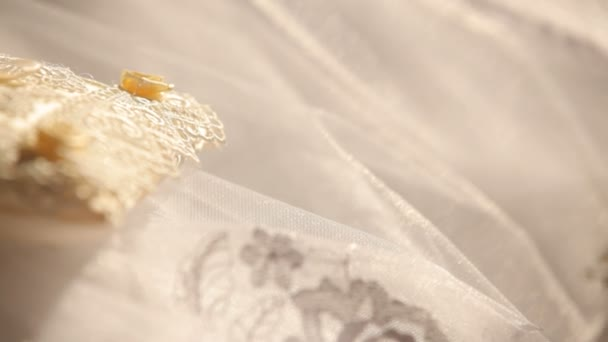 nevěsta ve svatebních šatech drží snubní prsteny