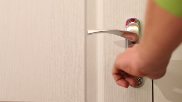 A male hand turns the key and opens the door