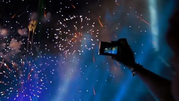 lidé natáčení krásné slavnostní ohňostroj na kamery. ohňostroje na obloze