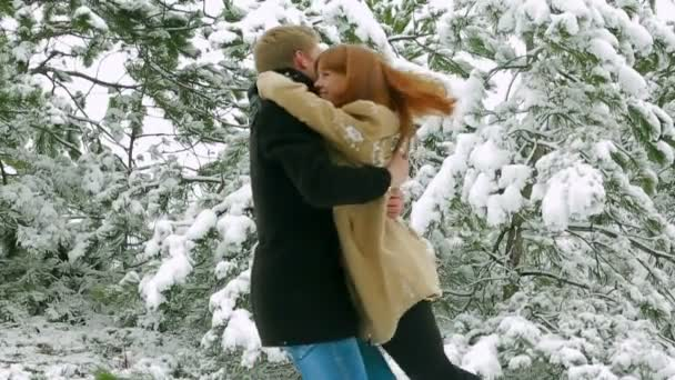 Couple in love in a snowy forest. Couple in a forest. Slow motion.
