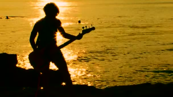 Playing guitar on the beach at sunset. Playing guitar.