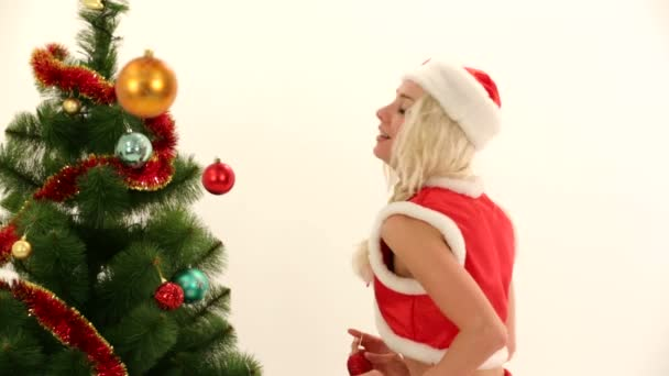 Woman in Santas costume decorating Christmas tree. Symbols of Christmas.