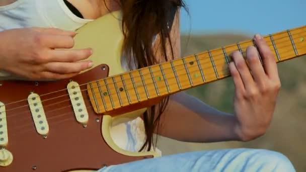 mladá žena hraje kytara. detail. kytarové akordy