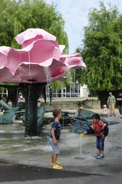 Children play near a fountain