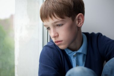 Sad teenager sitting on window