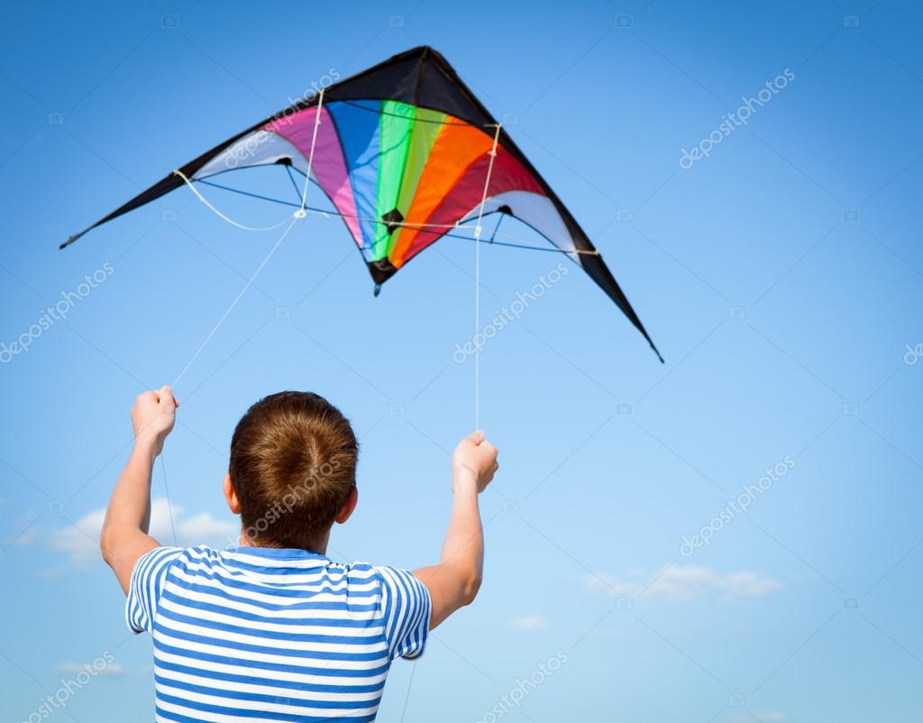 boy flies kite into blue sky