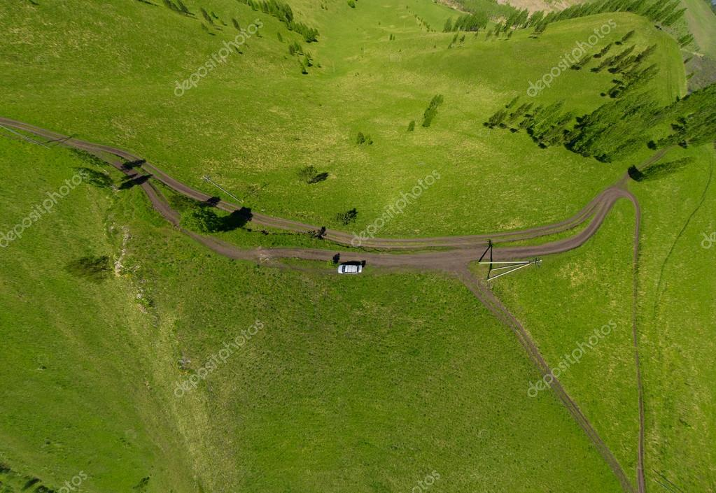 Beautiful small green mountain road with lake from above (aerial view)