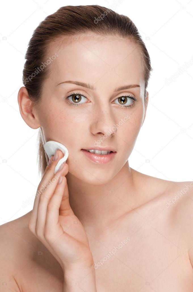 Closeup portrait of young beautiful woman with perfect skin. Applying clean sponge. Isolated