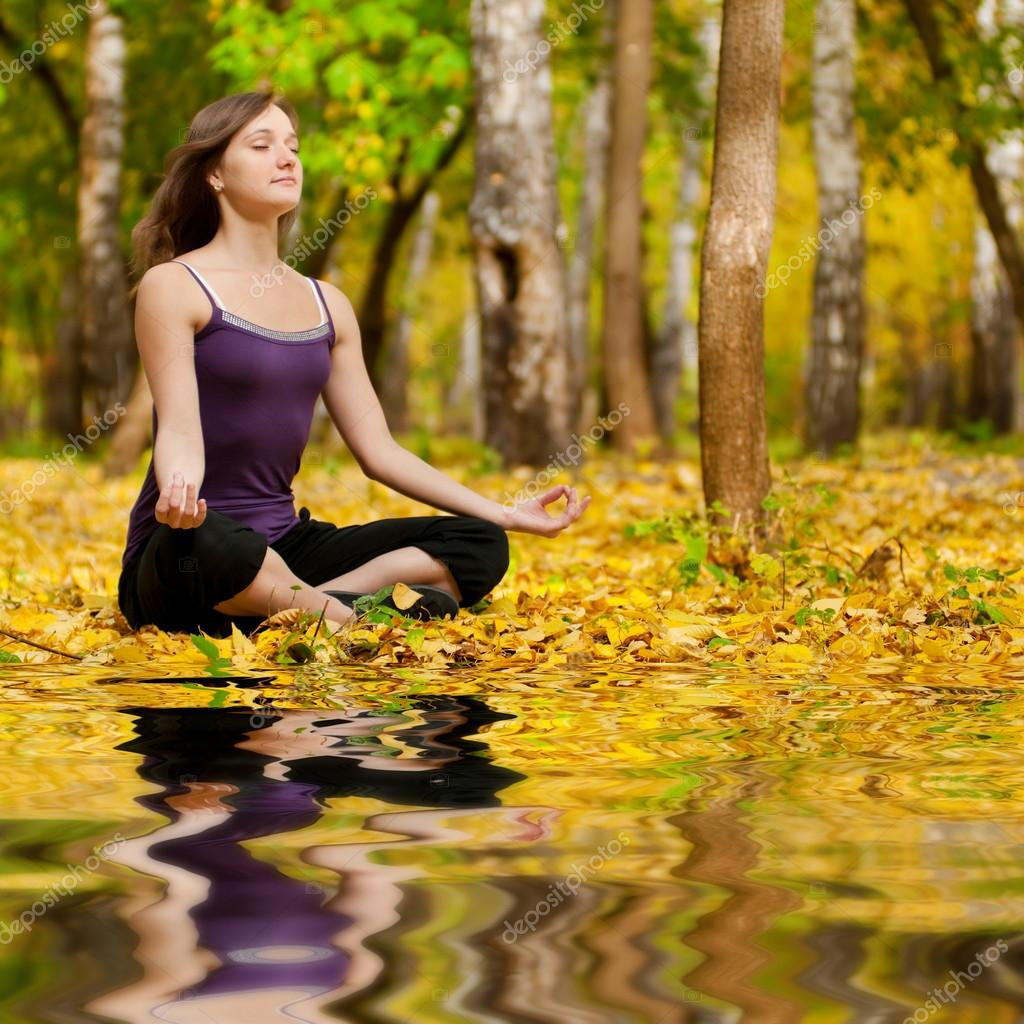 Woman doing yoga exercises in the autumn park