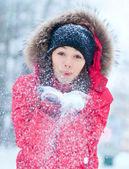 Glückliche junge frau spielt mit einem snow