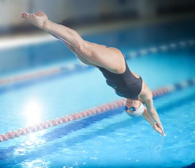 Female swimmer jumping into swimming pool