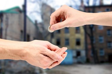 Hand gives coin to beggar on the street