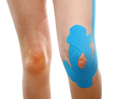 therapeutic treatment of leg with blue physio tape