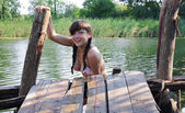 Young female mermaid on the wooden bridge