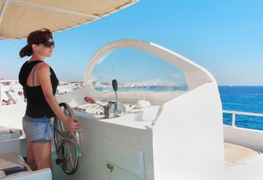 woman at the helm of yacht captain